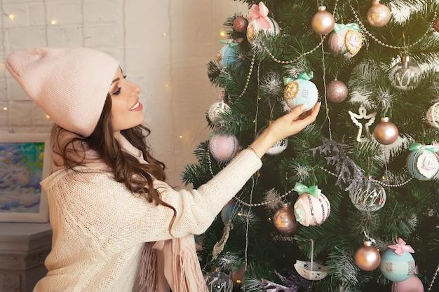Glückliche junge frau schmückt den weihnachtsbaum. mädchen in einem pullover, der einen weihnachtsbaum mit kugeln verziert. neujahrs- und weihnachtsferienkonzept.