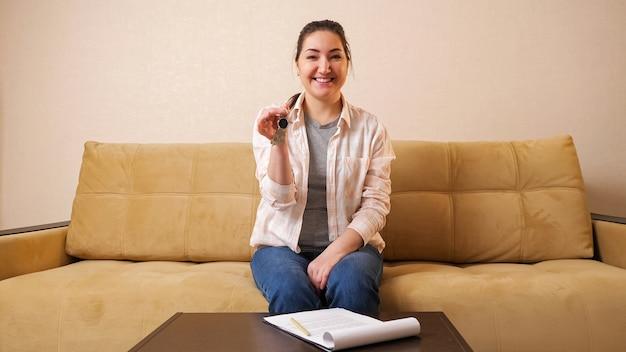 Glückliche junge frau schüttelt schlüsselbund über wohnungsmietvertrag an kleinem couchtisch, der auf bequemem sofa im hellen raum sitzt