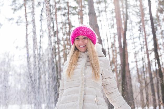 Glückliche junge frau spielt mit einem schnee am schneebedeckten wald im freien.