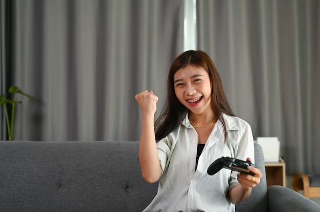 Glückliche junge frau spielt und gewinnt online-spiel, während auf dem sofa zu hause sitzen.