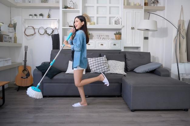Glückliche junge frau tanzt und putzt den boden mit mopp im wohnzimmer