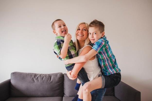 Glückliche junge frau umarmt ihre kinder
