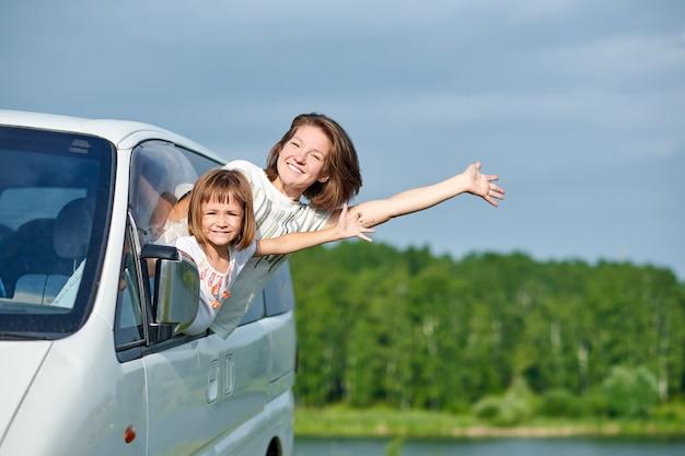 Glückliche junge frau und ihr kind, die heraus von den fenstern schauen. familie, die mit dem auto reist.
