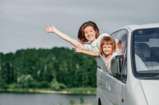 Glückliche junge frau und ihr kind schauen aus den fenstern. familie reist mit dem auto