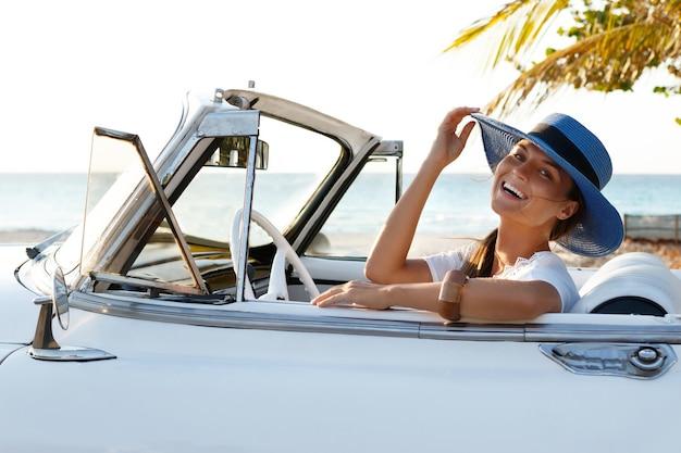 Glückliche junge frau und retro cabrio auto neben dem strand bei varadero stadt