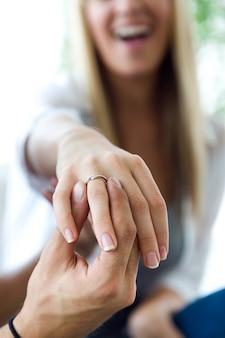 Glückliche junge frau, weil ihr freund einen verlobungsring gibt.