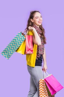 Glückliche junge frau, welche die einkaufstaschen stehen gegen lavendeloberfläche hält