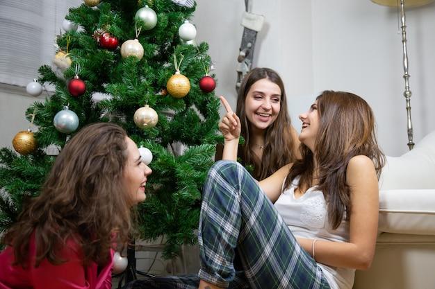 Glückliche junge frauen, die das sitzen auf dem boden nahe dem weihnachtsbaum sprechen