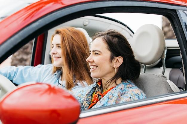 Glückliche junge frauen, die im auto sitzen