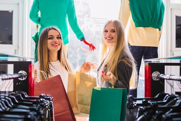 Glückliche junge frauen, die im bekleidungsgeschäft halten einkaufstaschen stehen