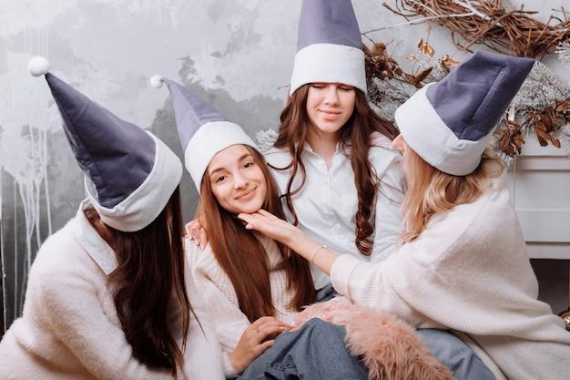 Glückliche junge frauen, die im kuscheligen kleidungsfeiertag der frauen tragen