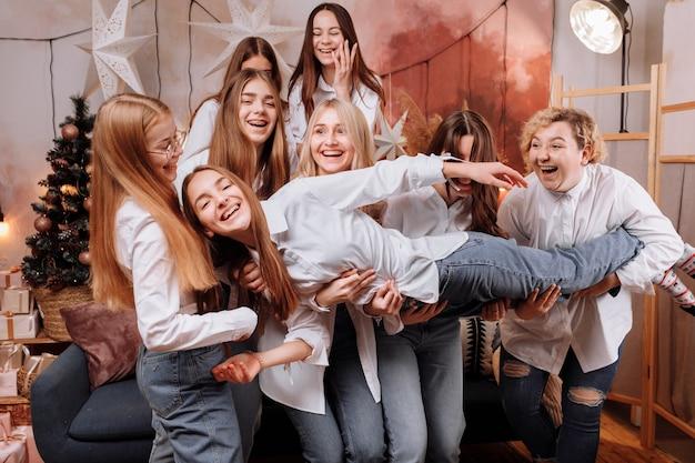 Glückliche junge frauen, die in den weißen hemden und in den jeansfeiertag tragen