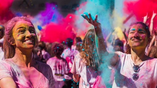 Glückliche junge frauen, die mit holi farben spielen