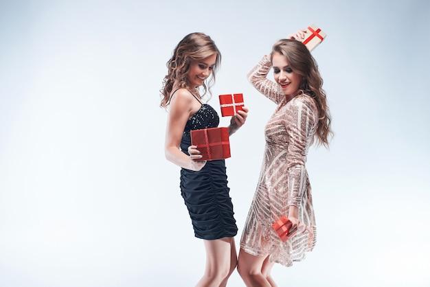 Glückliche junge frauen, die mit roten geschenken in den händen getrennt auf weiß tanzen