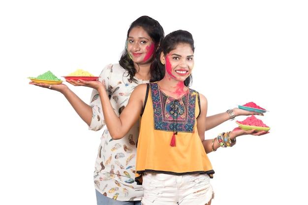 Glückliche junge frauen, die spaß mit buntem puder am holi festival der farben haben