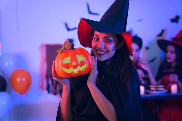 Glückliche junge frauen in den schwarzen hexen-halloween-kostümen in einer partei