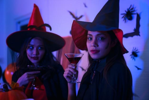 Glückliche junge frauen in schwarzen hexen-halloween-kostümen auf einer party mit kürbis und cocktails