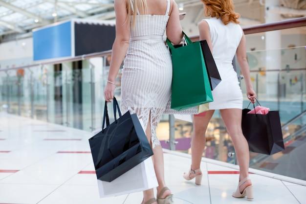 Glückliche junge frauen mit einkaufstüten genießen beim einkaufen, mädchen haben spaß mit ihren einkäufen. konsum- und lifestyle-konzept