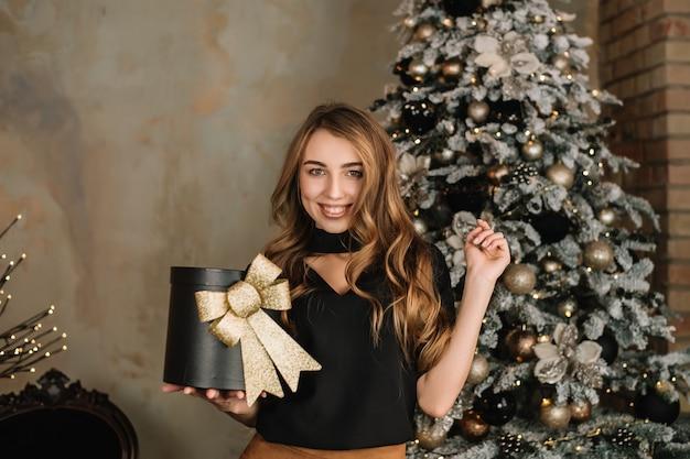 Glückliche junge frauen mit geschenk nahe thr weihnachtsbaum