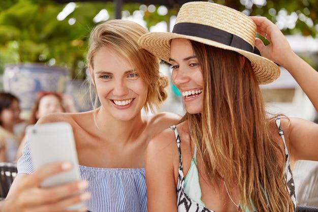 Glückliche junge frauen sehen interessante videos auf dem smartphone oder machen selfie, hat entzückenden blick, ruhen sich zusammen in der cafeteria im freien in der kurstadt aus. menschen-, beziehungs- und sommerruhekonzept