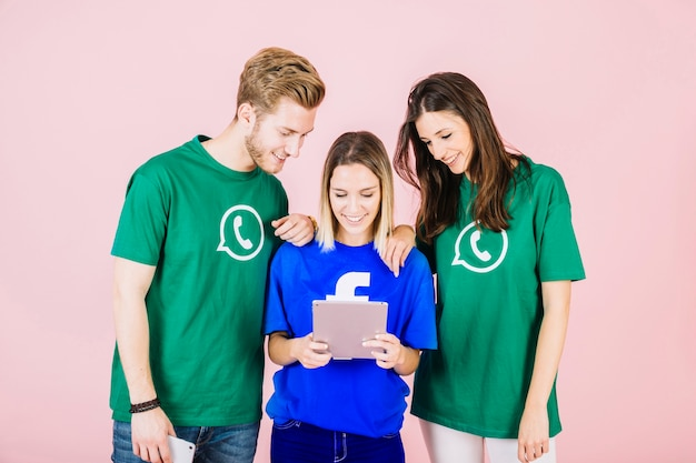Glückliche junge freunde, die digitale tablette betrachten