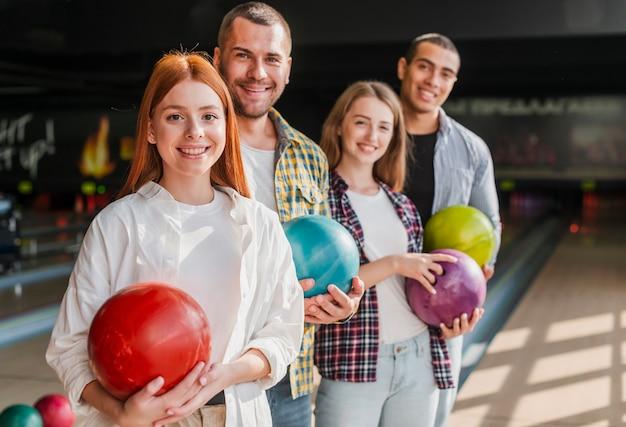 Glückliche junge freunde, die mittleren schuss der bowlingkugeln halten