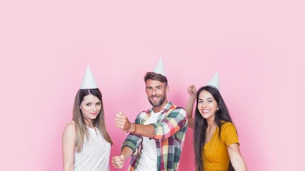 Glückliche junge freunde, die spaß auf rosa hintergrund haben