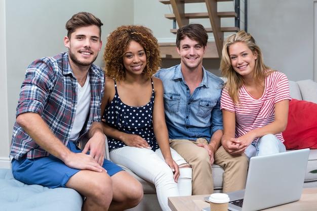 Glückliche junge freunde, die zu hause auf sofa sitzen
