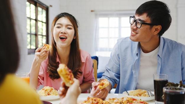 Glückliche junge freunde gruppe, die zu hause zu mittag isst. asia familienfeier, die pizza essen isst und lachend das essen genießt, während sie am esstisch zusammen im haus sitzt. festurlaub und zusammengehörigkeit.