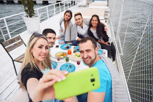 Glückliche junge freunde saßen an einem tisch und machten ein picknick im freien.
