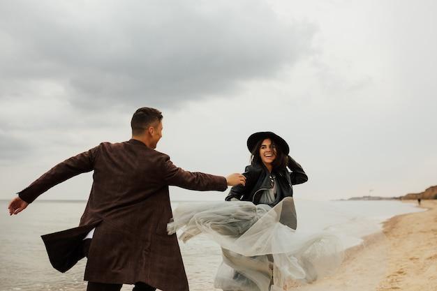 Glückliche junge frisch verheiratete paarfrau im blauen kleid mit schwarzem hut und mann im liebeslauf