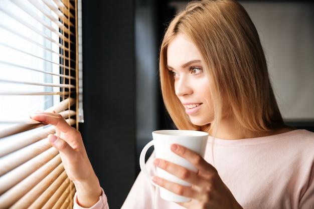 Glückliche junge fröhliche frau, die im café steht