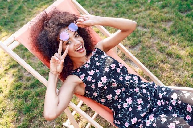 Glückliche junge gemischte begeisterte frau mit erstaunlichen lockigen haaren, die auf chaiselongue auf grünem rasen im park entspannen