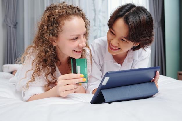 Glückliche junge gemischtrassige freundinnen, die auf bett mit tablet-computer liegen und online mit kreditkarte einkaufen