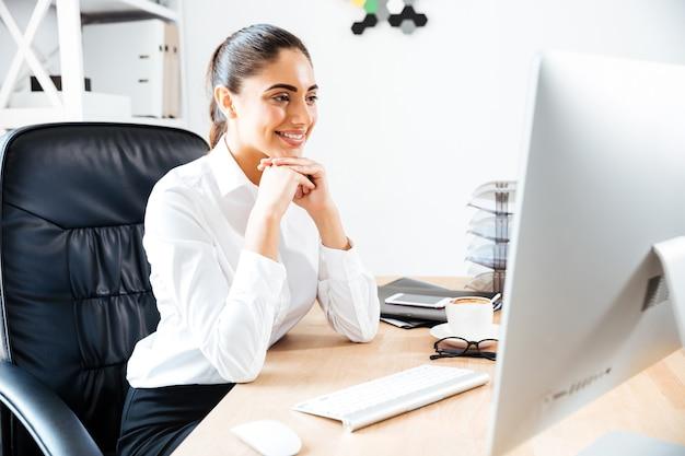 Glückliche junge geschäftsfrau, die auf den computerbildschirm schaut, während sie am bürotisch sitzt