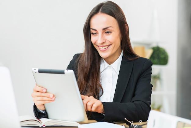 Glückliche junge geschäftsfrau, die digitale tablette im büro verwendet