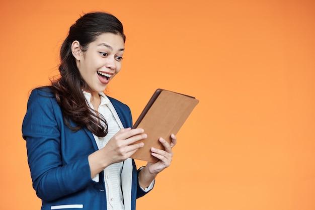 Glückliche junge geschäftsfrau, die dokument mit guten nachrichten auf tablet-computer liest