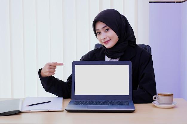 Glückliche junge geschäftsfrau, die einen laptop auf dem schreibtisch zeigt