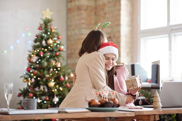 Glückliche junge geschäftsfrau, die ihre kollegin umarmt, während sie ein weihnachtsgeschenk auf einer firmenfeier in der büroumgebung gibt