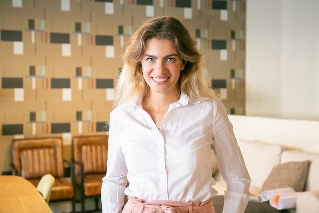 Glückliche junge geschäftsfrau, die im co-working- oder coffee-shop-interieur steht und posiert und kamera und lächeln betrachtet