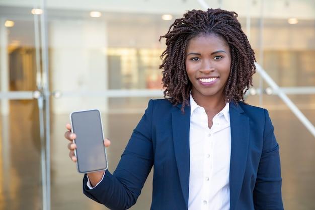 Glückliche junge geschäftsfrau, die smartphone zeigt