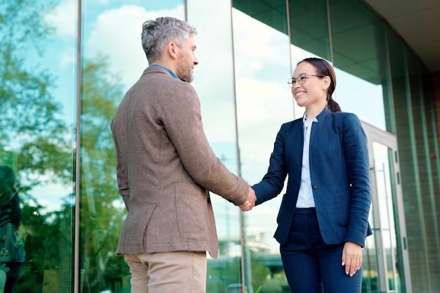 Glückliche junge geschäftsfrau händeschütteln ihres kunden nach abschluss eines vertrags oder vertragsunterzeichnung im stehen am bürogebäude