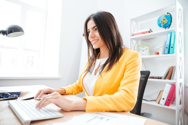 Glückliche junge geschäftsfrau mit tastatur und computermaus im büro
