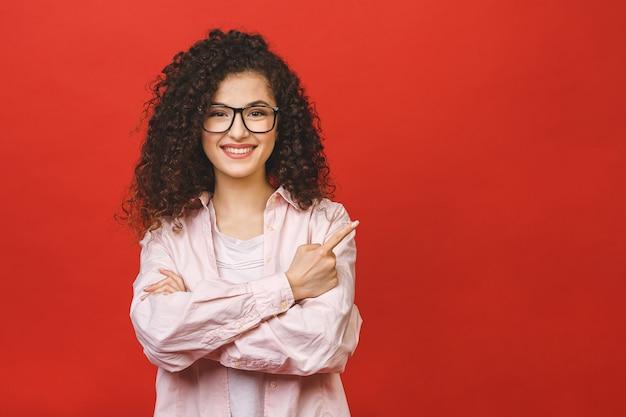 Glückliche junge geschäftsfrau mit verschränkten armen und schönem großen lächeln mit gesunden zähnen. isoliertes porträt über rotem hintergrund. zeigender finger.
