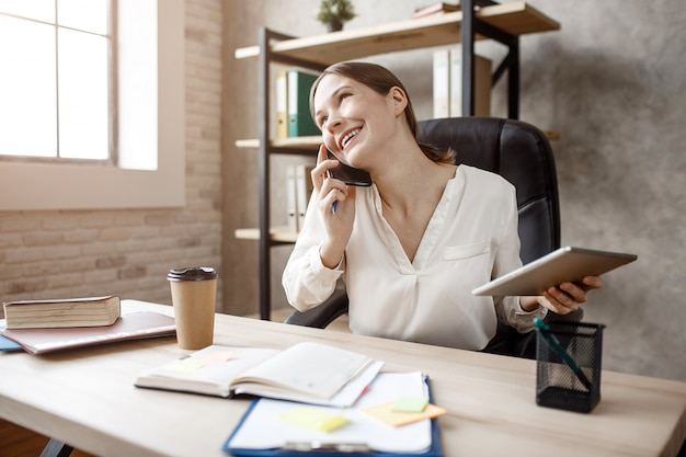 Glückliche junge geschäftsfrau sitzen am tisch im zimmer und arbeiten. sie telefoniert und lächelt. model hold tablet. tageslicht.