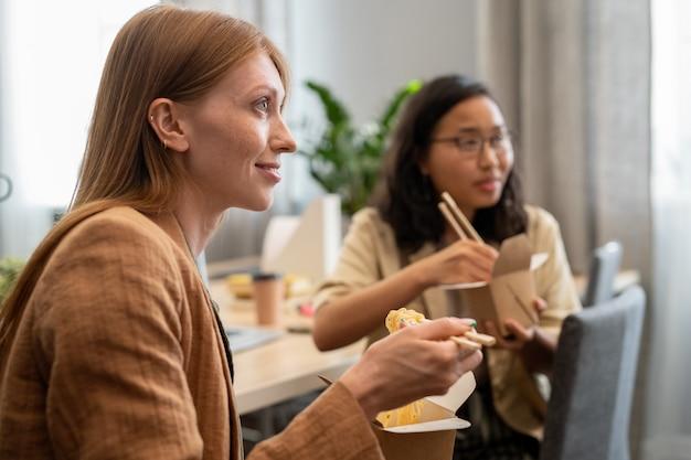 Glückliche junge geschäftsfrau und ihr kollege, die chinesischen wok essen