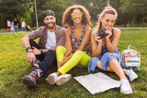 Glückliche junge gesellschaft der sprechenden lächelnden freunde, die park, mann und frauen sitzen, die spaß zusammen haben und mit kamera reisen