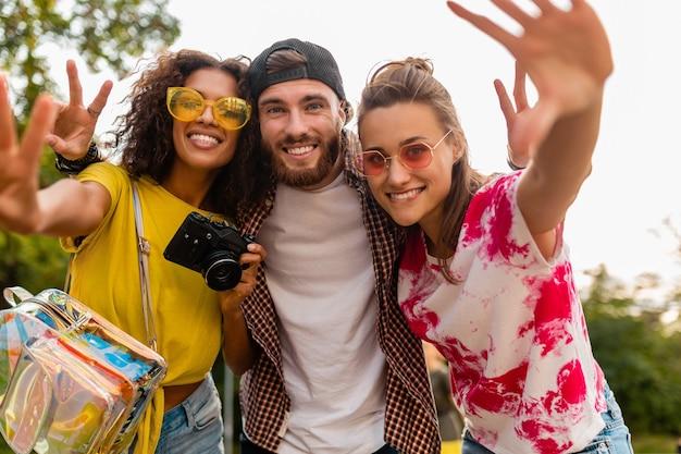 Glückliche junge gesellschaft von emotional lächelnden freunden, die im park mit fotokamera, mann und frauen gehen, die spaß zusammen haben
