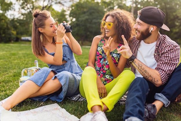 Glückliche junge gesellschaft von freunden, die park, mann und frauen sitzen, die spaß zusammen haben, bunte sommer-hipster-modestil, das reisen, das foto vor der kamera nimmt, spricht, lächelt