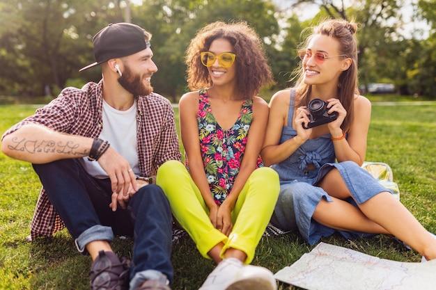 Glückliche junge gesellschaft von freunden, die park, mann und frauen sitzen, die spaß zusammen haben, bunte sommer-hipster-modestil, mit kamera reisend, sprechend, lächelnd